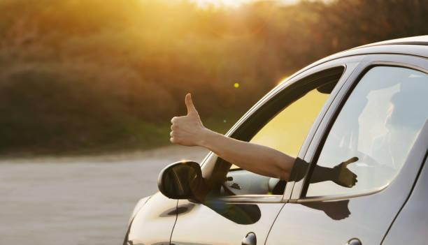 gün batımında araba penceresinden başparmak kadar gösteren adam - thumbs up stok fotoğraflar ve resimler
