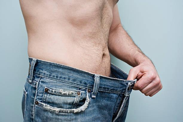 Mann zeigen Gewicht Verlust, indem es seine lässige Hose – Foto