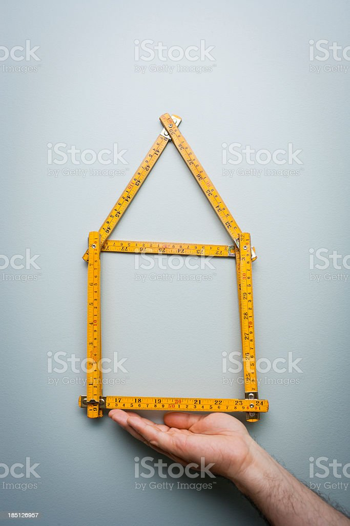 Man shows a folding ruler in the shape of a home stock photo