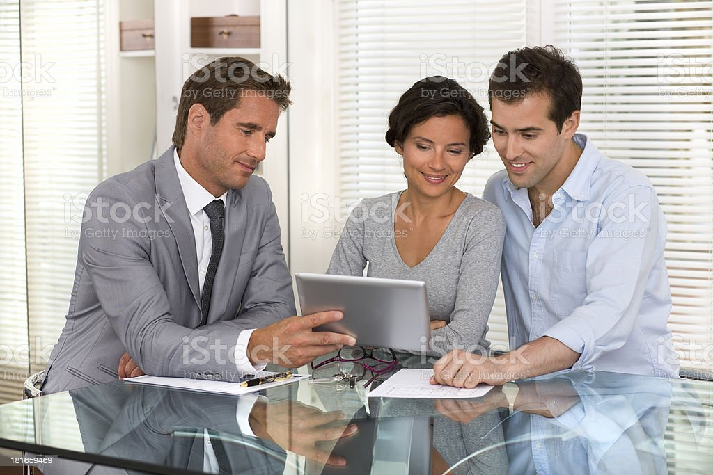 Man shows couple a presentation on tablet PC royalty-free stock photo