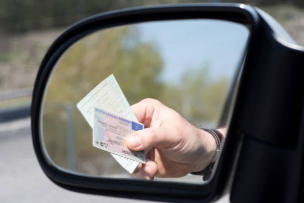 ein mann zeigt führerschein und fahrzeugschein bei einer kontrolle - führerschein stock-fotos und bilder