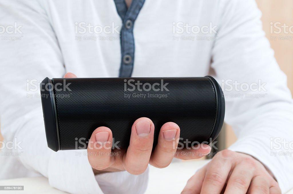 Man shows Modern wireless audio device. stock photo