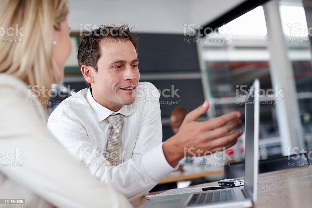 Man shows plans on the laptop to colleague during meeting royalty-free stock photo