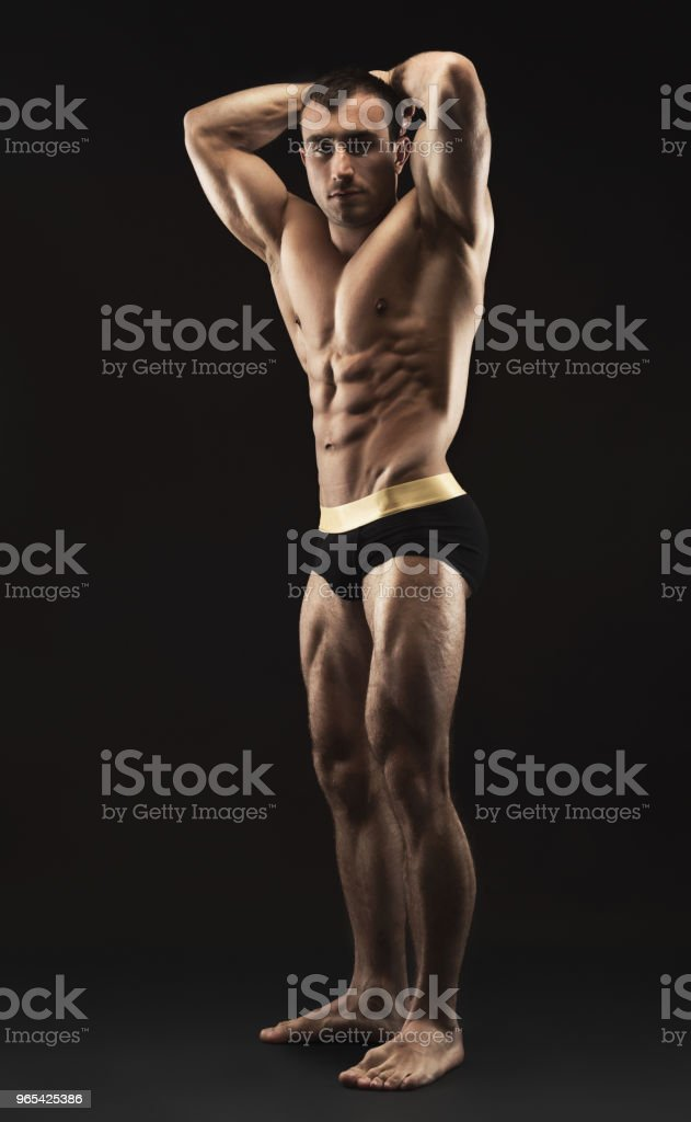 Man shows strong body and muscles at black background royalty-free stock photo