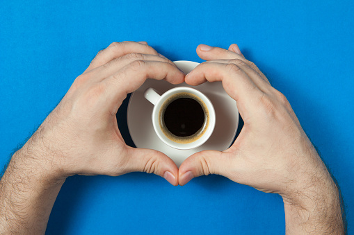 Man shows the shape of the heart with his hands on a cup of coffee over flatlay. Concept photo of the start of a new good day. Concept flat lay design for banner or blog.