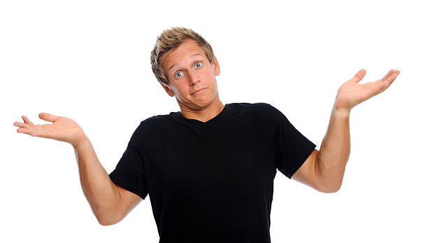 Man shrugs shoulders Young man shrugs and raises his arms helplessly isolated on white shrugging stock pictures, royalty-free photos & images