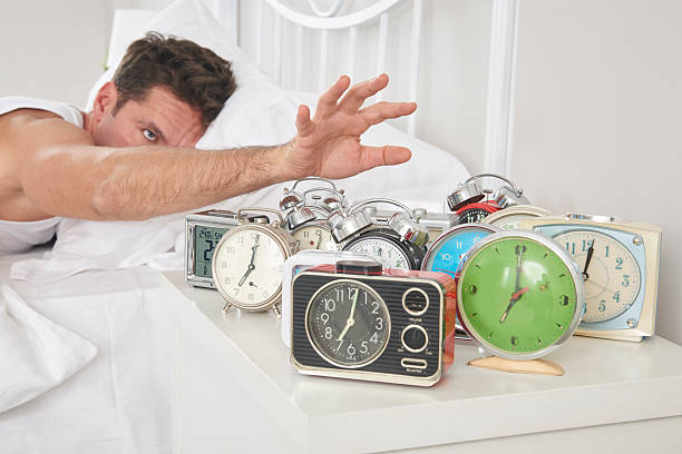 man shutting off alarm clocks - man face down stock pictures, royalty-free photos & images