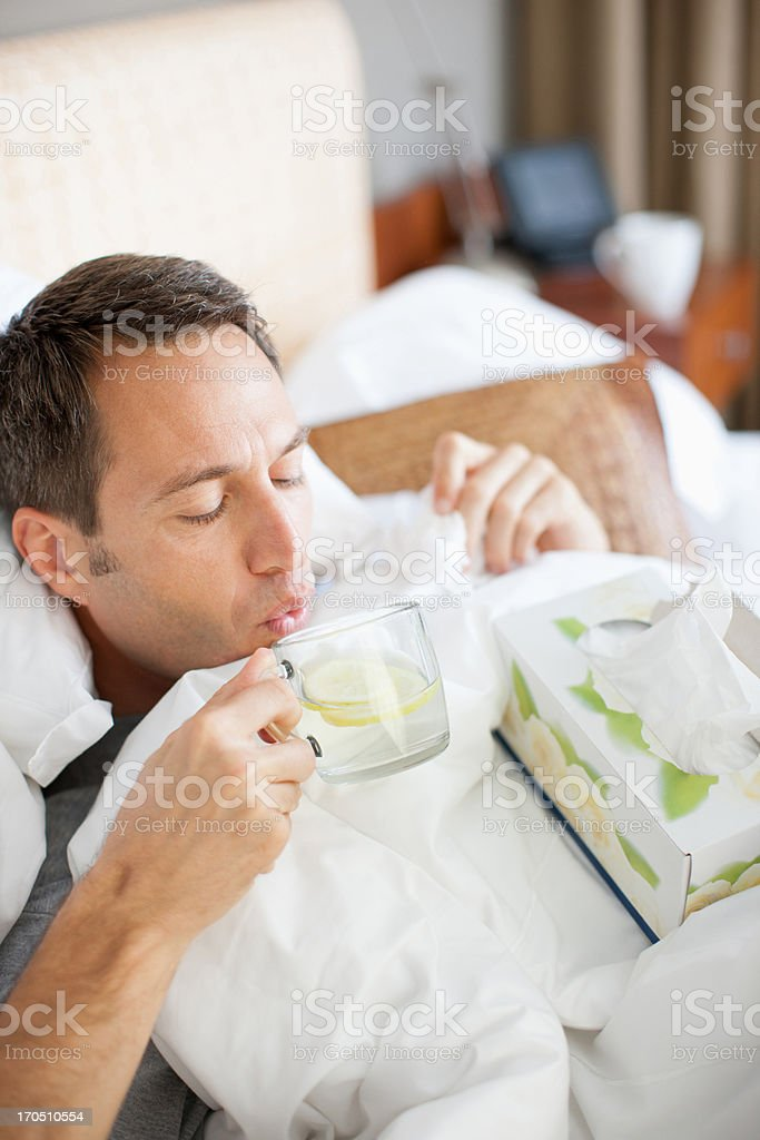Man sick in bed drinking hot drink royalty-free stock photo