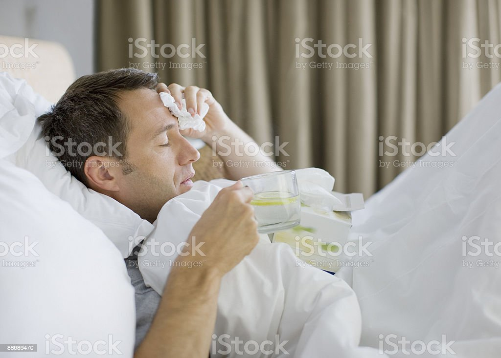 Man sick in bed drinking hot drink stock photo