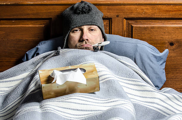 man sick in bed with a thermometer in his mouth stock photo