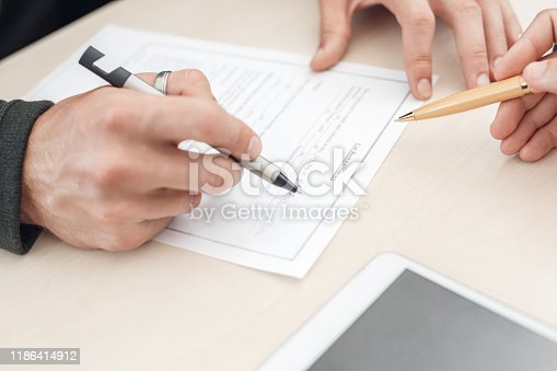 136591850 istock photo Man signature document to buying new car in auto salon 1186414912