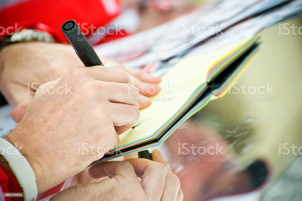 Man signing autograph in a book stock photo