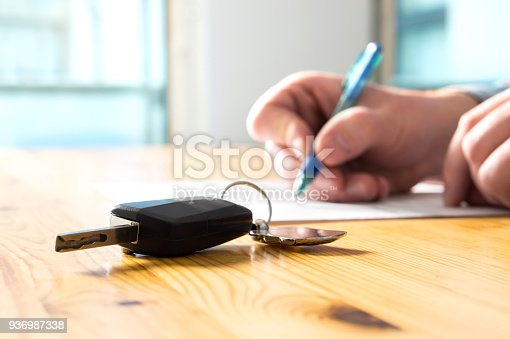 istock Man signing car insurance document or lease paper. Writing signature on contract or agreement. Buying or selling new or used vehicle. Car keys on table. Warranty or guarantee. 936987338