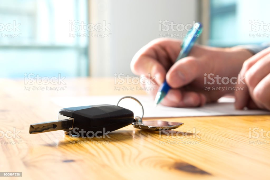 Man signing car insurance document or lease paper. Writing signature on contract or agreement. Buying or selling new or used vehicle. Car keys on table. Warranty or guarantee. - foto stock