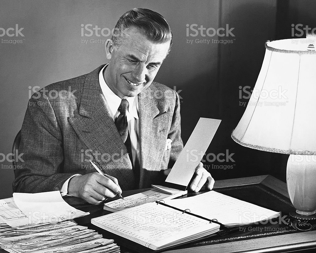 Man signing checks royalty-free stock photo