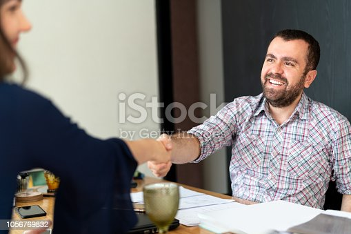 istock Man signing contracts and handshake with a business woman 1056769832