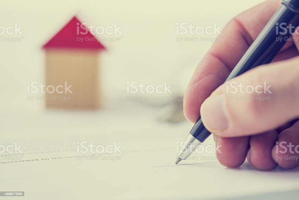 Man signing deed of sale on a house stock photo