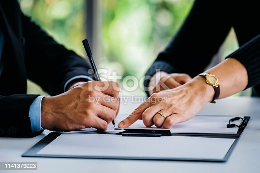 1072035844istockphoto Man signing documents near woman at table 1141379223