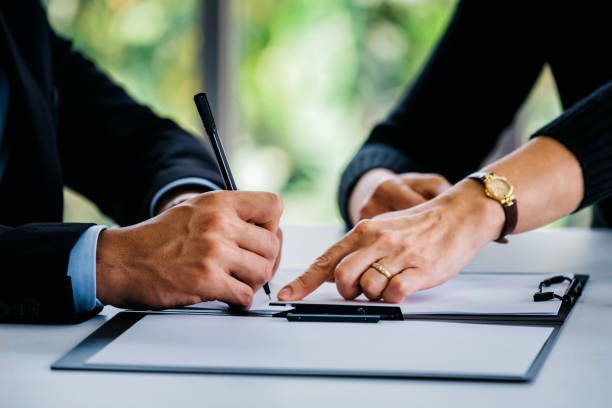 Man signing documents near woman at table stock photo