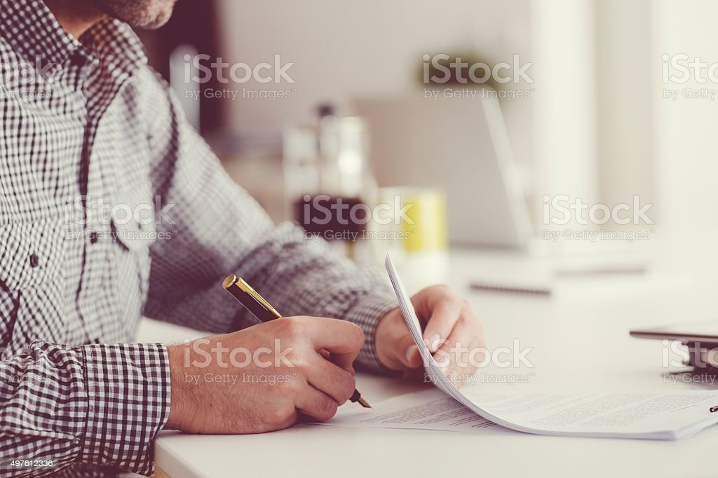 Man sitting at the table, holding a pen and signing contract. Focus...