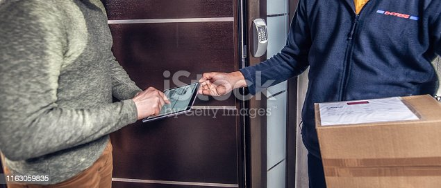 Courier holding package and tablet while male customer is signing receipt for his home delivery parcel.