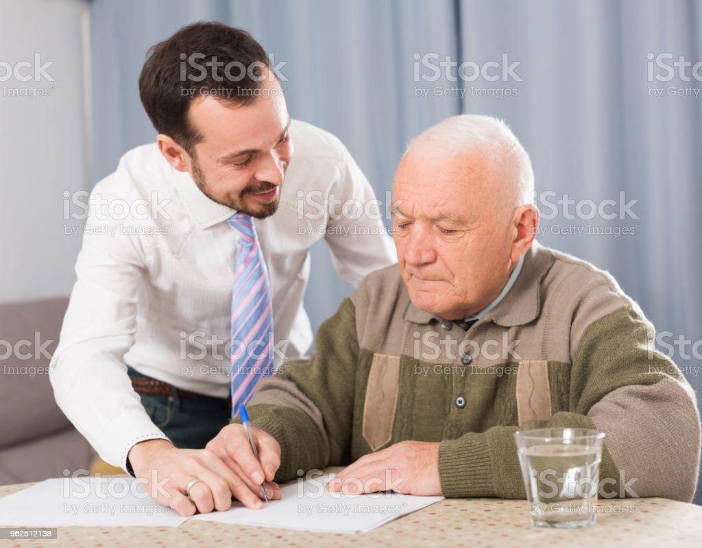 Homem assinando papéis em casa - Foto de stock de Acordo royalty-free