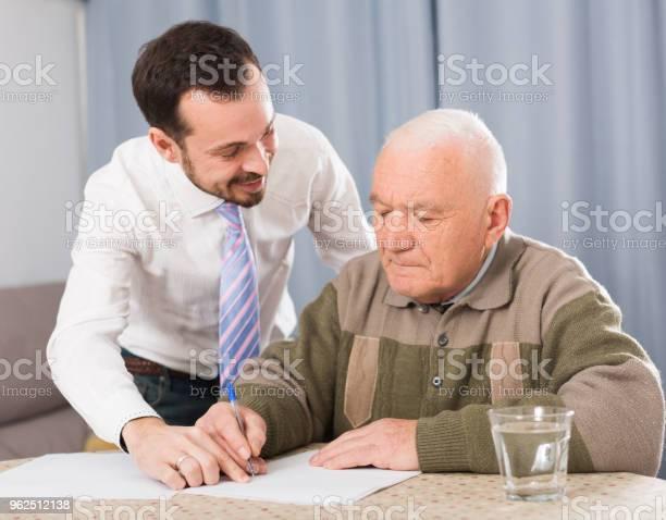 Foto de Homem Assinando Papéis Em Casa e mais fotos de stock de Acordo