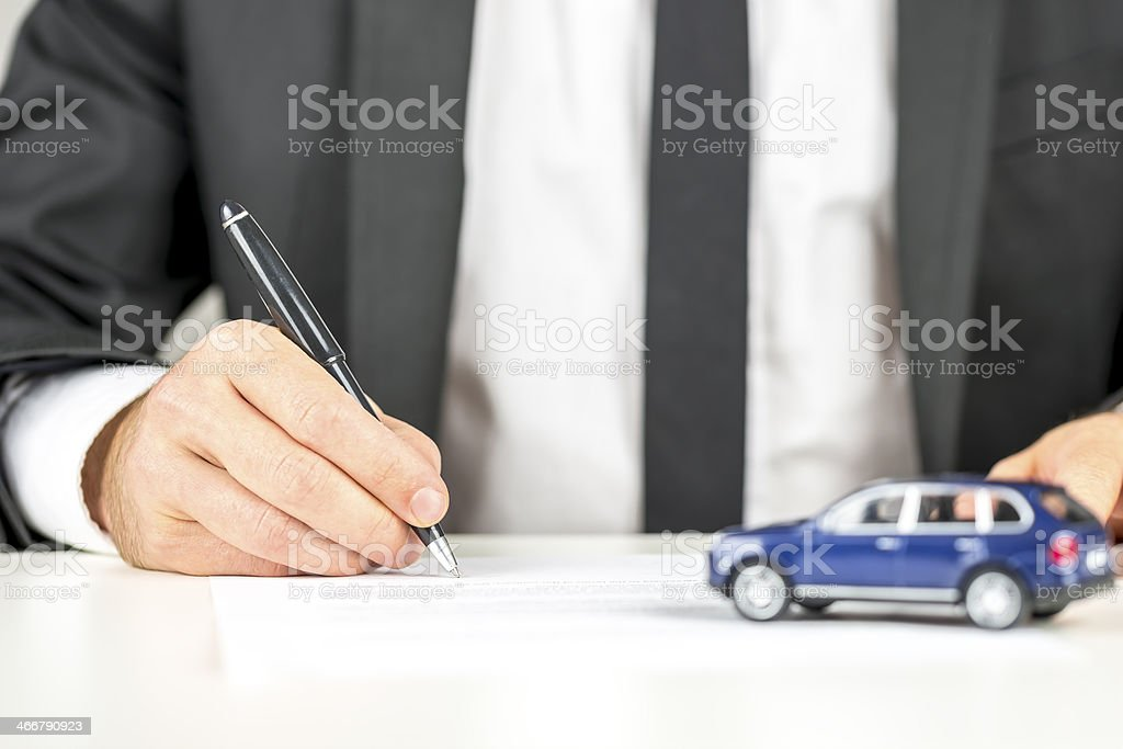 Man signing paperwork for new car purchase stock photo