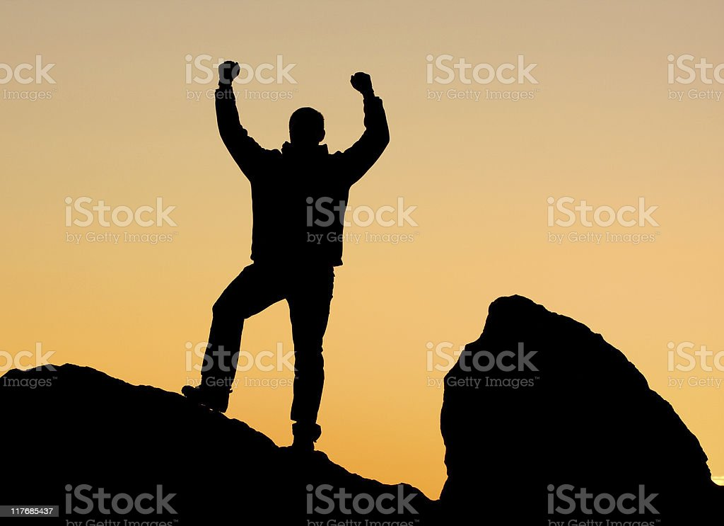 Man silhouette at sunset on rocks. royalty-free stock photo