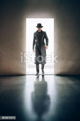 istock Man silhouette coming from the light of opening door in dark room 820870310