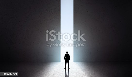 82186105 istock photo Man silhouette in front of opening concrete doors 1165267708