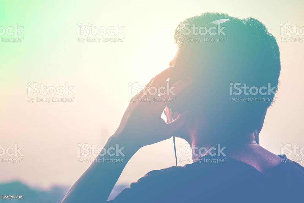 Man silhouette listening to the headphones on the sunset landscape background, Soft and sweet tone stock photo