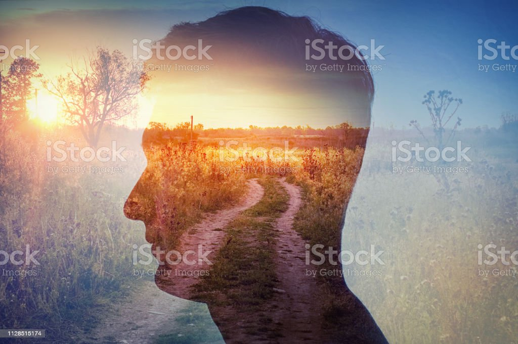 Man silhouette on rural landscape background. Psychiatry and psychology concept. stock photo