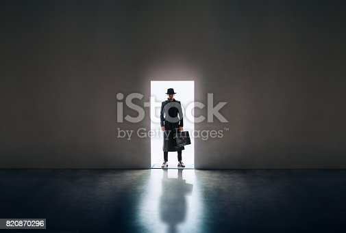 istock Man silhouette standing in the light of opening door in dark room 820870296