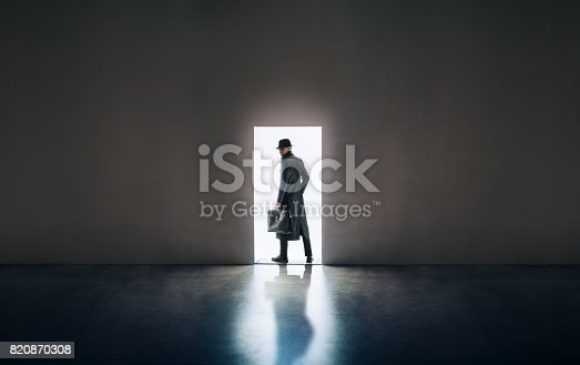 istock Man silhouette standing in the light of opening door in dark room 820870308