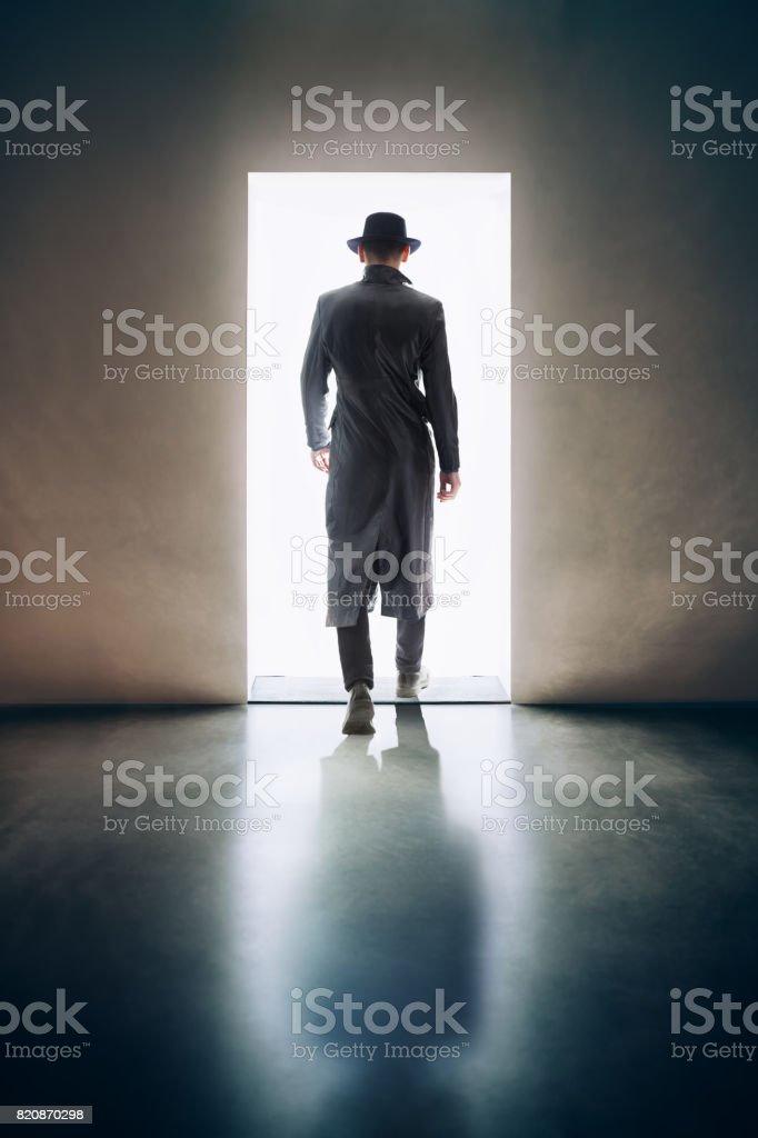 Silhouette d'homme s'éloignant à la lumière de l'ouverture de porte dans la chambre noire - Photo