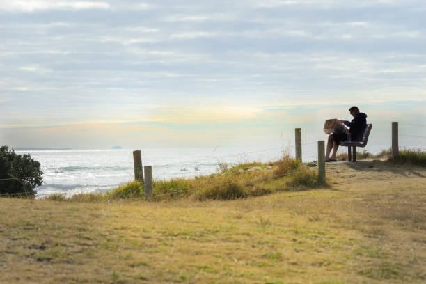 man silhouetten door morning sun zit het lezen van de baai van de vele malen - newspaper beach stockfoto's en -beelden