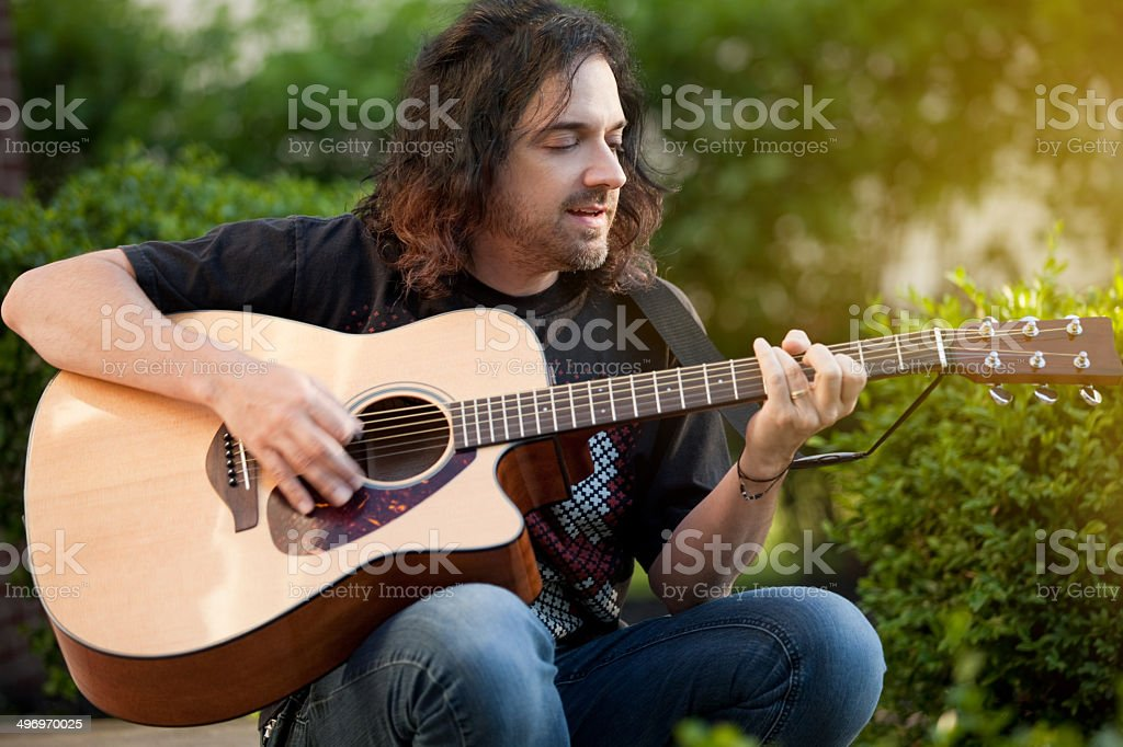 Man Singing And Playing Guitar Outdoors royalty-free stock photo
