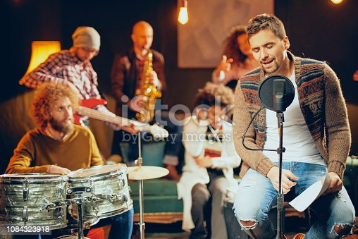 849362192 istock photo Man singing and sitting on chair. 1084323918