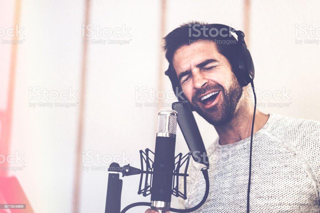 Mann singt in Mikrofon im Tonstudio – Foto