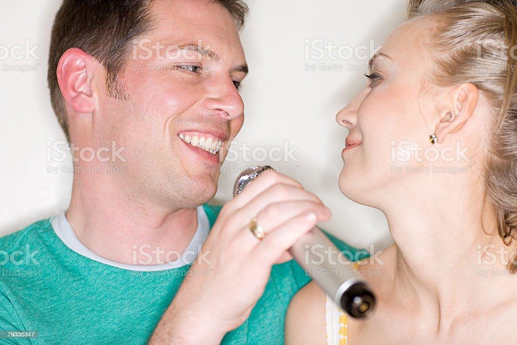 Man singing karaoke to woman 免版稅 stock photo