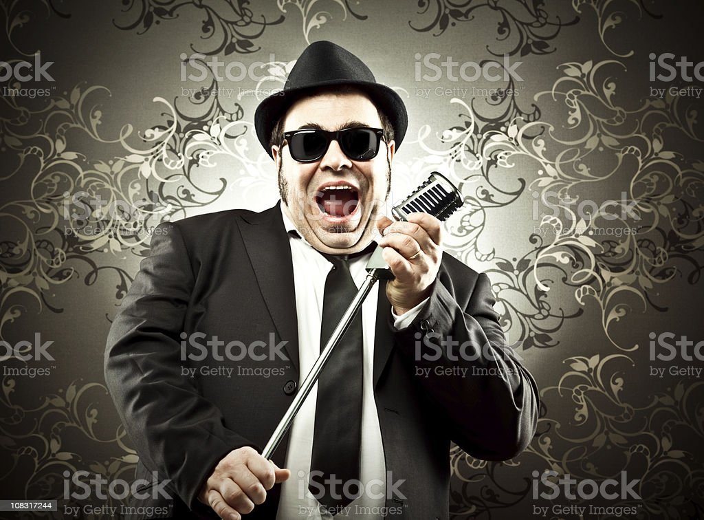man singing with microphone stock photo