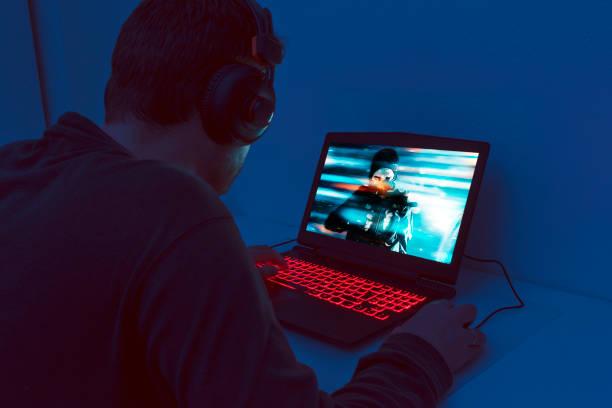 男一人でゲームのノート パソコンの前に座るし、ビデオ ゲームを果たしています。 - ゲーム ヘッドフォン ストックフォトと画像