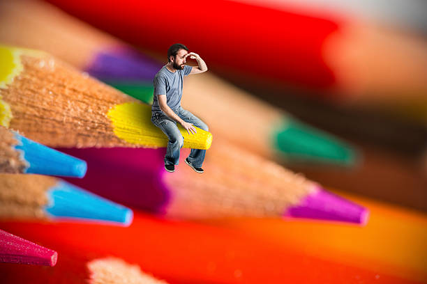 Man sit on crayons looking out stock photo