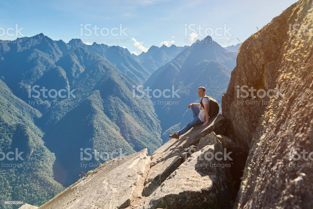 Man sit on mountain peak - foto de acervo
