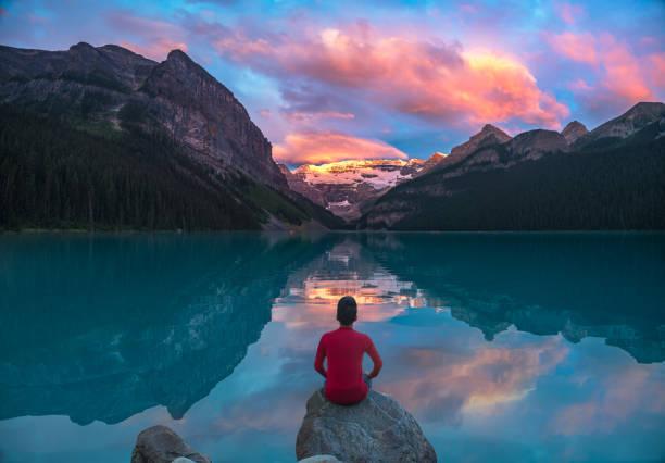 homme assis sur rocher, regarder les nuages matin lake louise aux reflets - paysage zen photos et images de collection