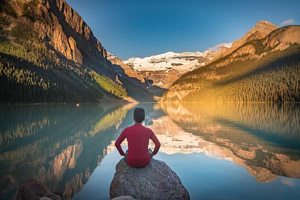 Man sit on rock watching Lake Louise reflections stock photo