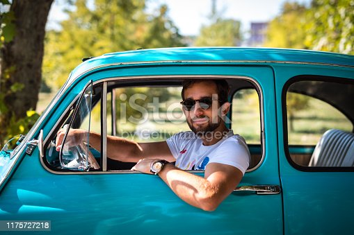 Man siting in vintage car on the road