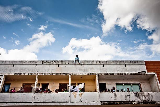 Homem sentado sozinho no topo de um edifício. - foto de acervo