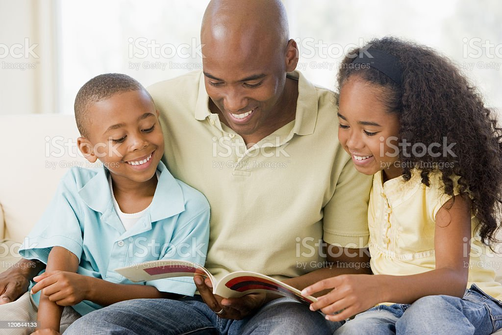 Man sits and reads a book with two children stock photo